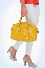 Composite image of woman in high heels walking with yellow bag