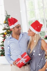 Composite image of smiling couple at christmas