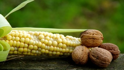 Corn and walnuts on wooden table