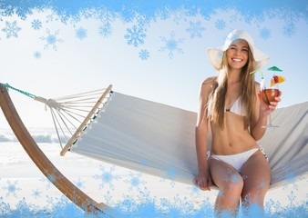 Smiling blonde wearing sunhat sitting on hammock with cocktail