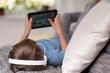 junge liegt auf dem sofa und spielt mit tablet-pc