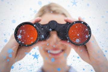 Composite image of woman looking through binoculars