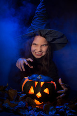 The little witch with halloween pumpkin