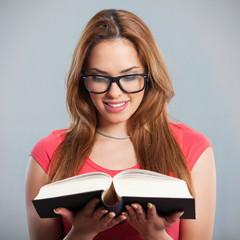 Beautiful young woman reading a book. Studio Shot