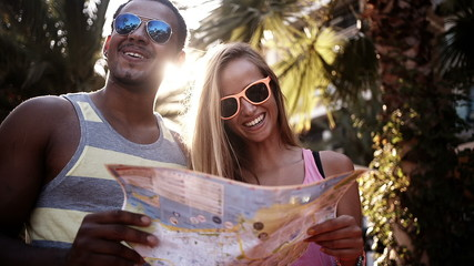 Mixed racial couple looking at map of city together