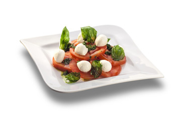 Artistically arranged tomato salad with mozzarella garnished wit