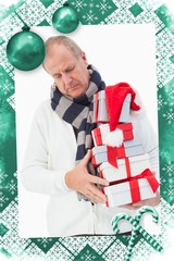Composite image of mature man in winter clothes holding gifts