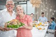 Grandparents holding chicken roast with family