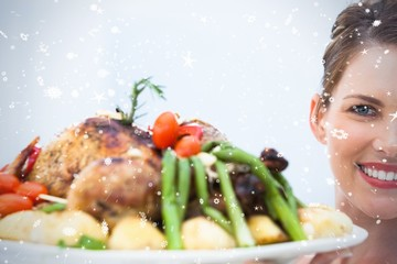 Smiling woman showing roast chicken