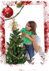 Father holding her daughter to decorate the tree