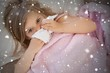 Composite image of girl suffering from cold as she lies in bed
