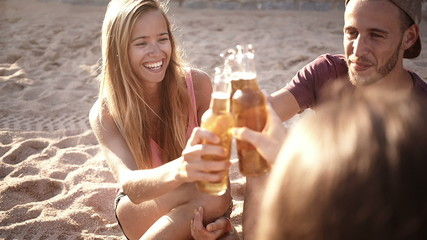 Friends sitting on beach and cheers before drinking beers