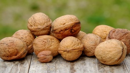 Walnuts on wooden table and green background