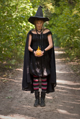 Halloween Witch with Flaming Pumpkin in the Forest