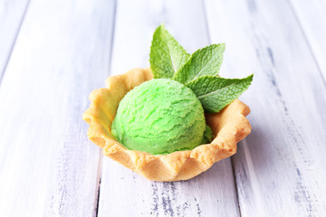 Green ice cream  ball in wafer bowl on color wooden background