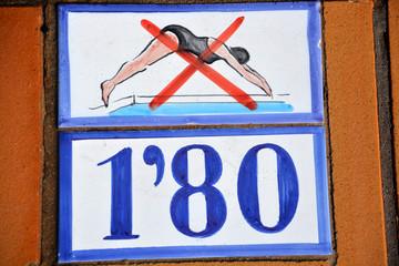 cartel indicador de peligo por poca profundidad en piscina