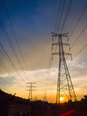 high voltage power pylons in sun set
