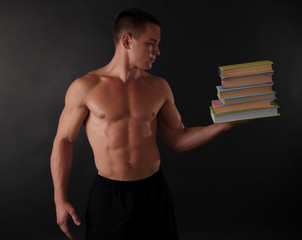 Handsome muscle young man handing books on dark background