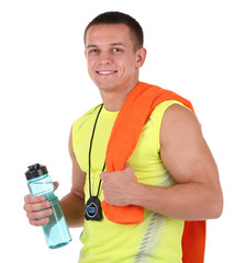 Handsome young sportsman holding towel and bottle with water