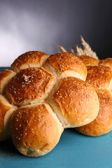Tasty buns with sesame on color wooden table, on gray