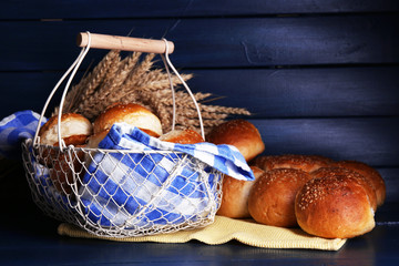 Tasty buns with sesame in  basket, on color wooden background
