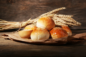 Tasty buns with sesame on wooden background