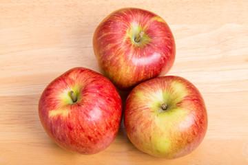 Three Red Apples on Wood Table