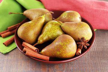 Ripe pears and cinnamon sticks in bowl,