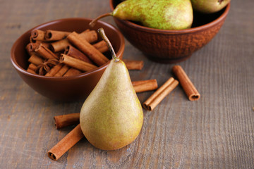 Ripe pears and cinnamon sticks in bowls, on wooden background