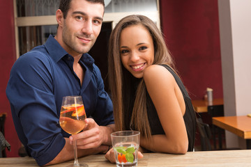 Smiling young couple drinking a cocktail in a bar.