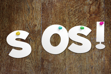 Word SOS cut out of paper