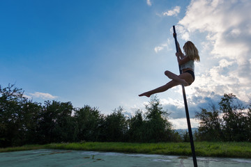 Silouette woman pole dancer performing outdoors against blue clo
