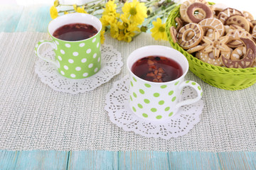 Two polka dot cups of tea with biscuits on fabric background