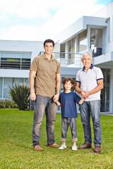 Kind mit Vater und Großvater vor Haus