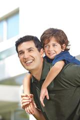 Glücklicher Vater trägt Sohn auf Rücken
