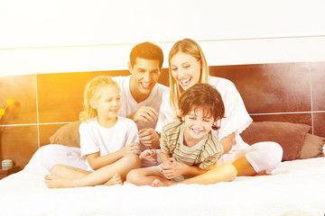 Lachende Familie sitzt im Bett