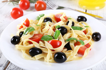 Spaghetti with tomatoes, olives and basil leaves