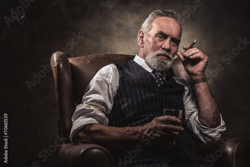 In chair sitting senior business man with cigar and whisky. Gray - 70661539