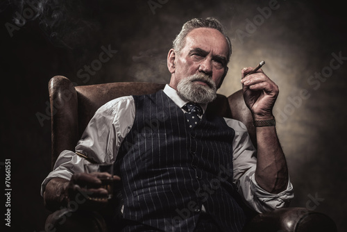 Leinwandbild Motiv In chair sitting senior business man with cigar and whisky. Gray