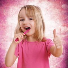 kleines süßes Mädchen mit Zahnbürste und Daumen hoch