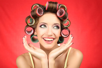 Beautiful girl in hair curlers on red background