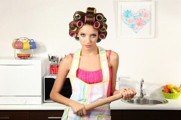 Beautiful girl in hair curlers in kitchen