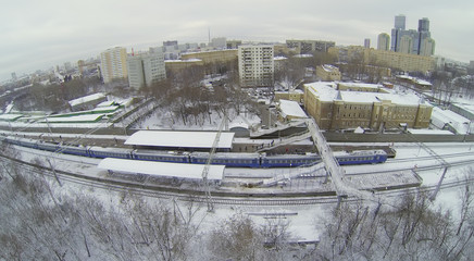 Train at snow-covered railway platform with pedestrian bridge
