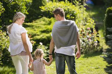 Junge Familie im Garten spazieren Hand in Hand