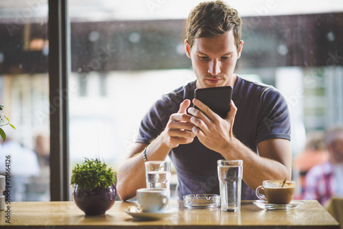 Leinwanddruck Bild Young man watching tablet in cafe