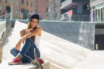 Smiling teenager with skateboard portrait outdoors.