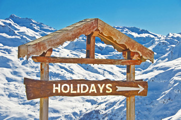 Rustic wooden sign direction holidays, snowy mountain landscape