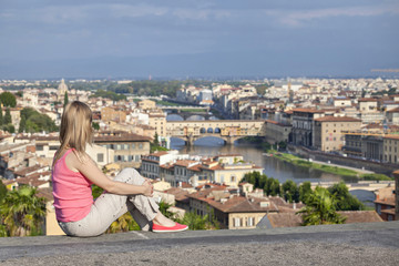 Girl is sitting on a background of the Ponte Vecchio bridge