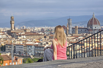 Blonde girl sitting on the stairs against Florence skyline