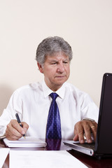 Mature businessman working with laptop in his office
